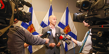 Dr. Tim Holland surrounded by reporters and cameras