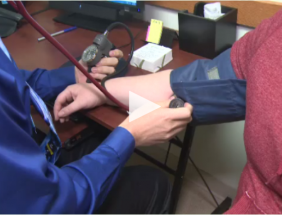 A health professional uses a blood pressure cuff on a patient.